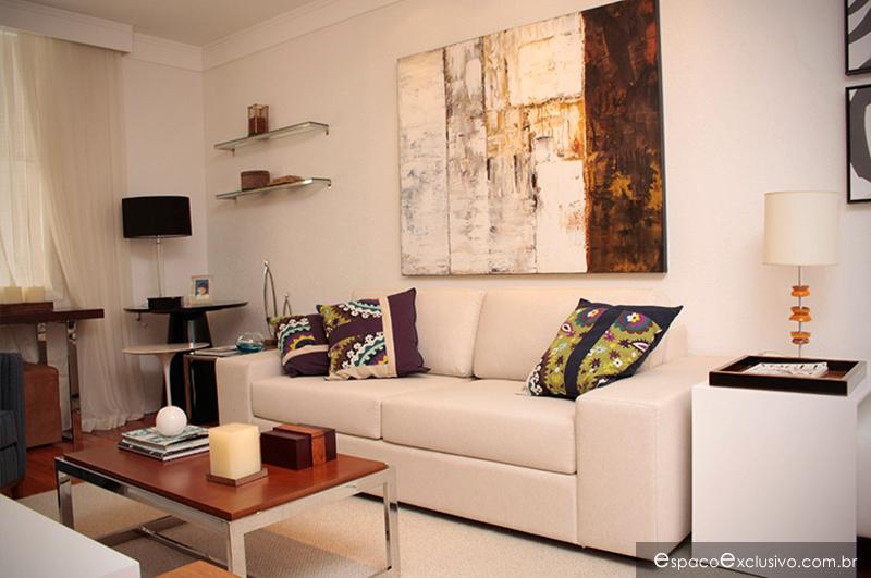 Sala de home com Sofá estofado, mesa de centro em aço inox e composição de quadros e almofadas.