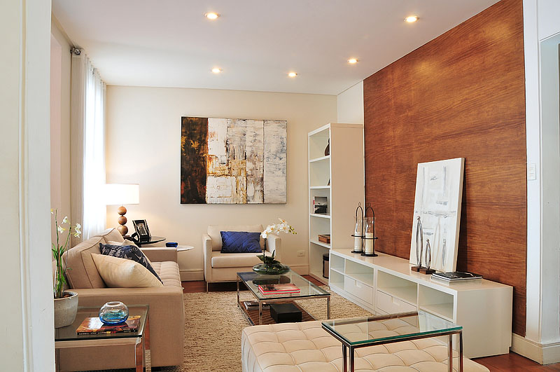 Uma perfeita sala de leitura. Pufe, sofá, rack, poltrona, mesa de centro, mesa lateral e uma estante.
