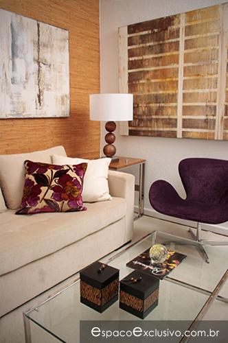 Ambiente composto por sofá estofado, mesa de centro em aço inox, tela de Ana Verona e destaque para poltrona Swan roxa.