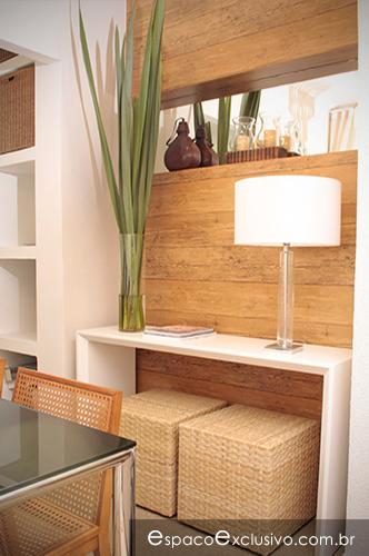 Ambiente com papel de parede de madeira de demolição, puffs em fibra e aparador em laca